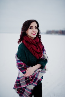 Brunette girl in green sweater and red scarf with plaid outdoor frozen lake on evening winter day.