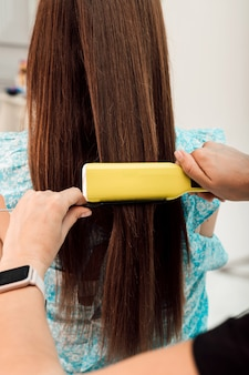 Парикмахер брюнетка девушка делает укладку