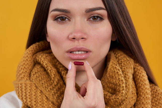 Brunette girl has cold poses with pills on yellow background