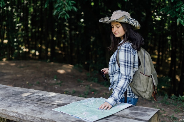 Brunette girl in hat with tourist map in summer forest.