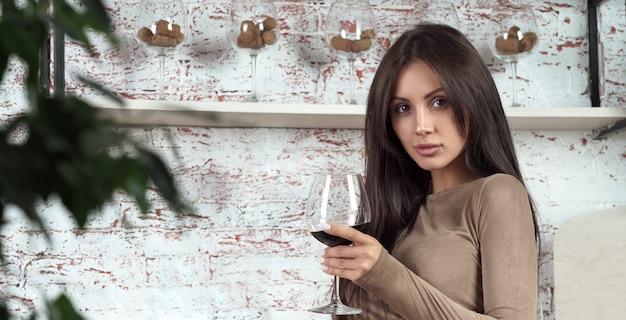 Брюнетка девушка держит бокал красного вина на кухне с копией пространства