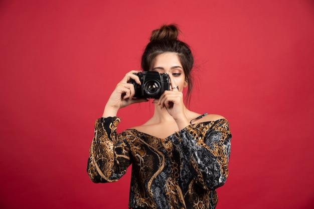 Девушка брюнетка держит профессиональную камеру dslr и делает фотосессию.