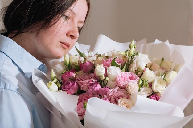 큰 핑크 장미 꽃다발을 들고 침대에서 즐기는 갈색 머리 소녀
