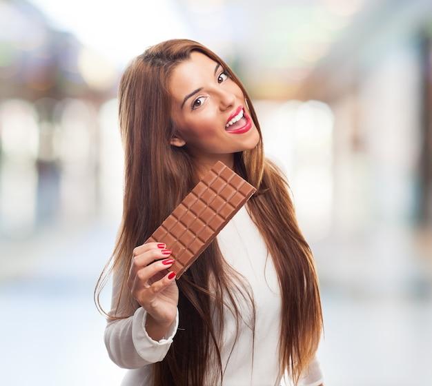 ブルネットの少女はおいしいチョコレートを保持しています。