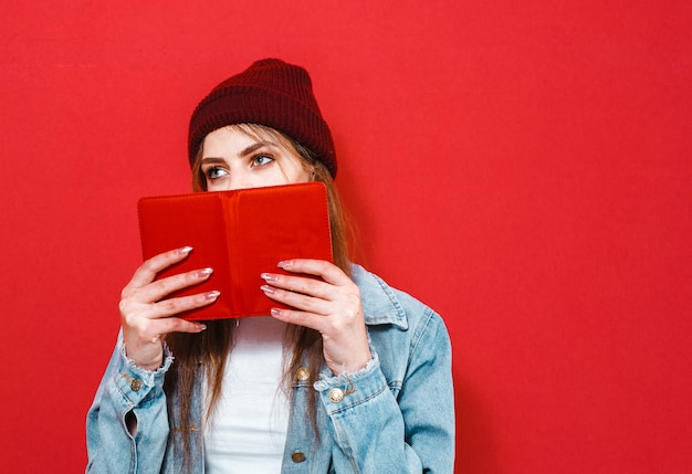 A brunette girl holding her face with a book