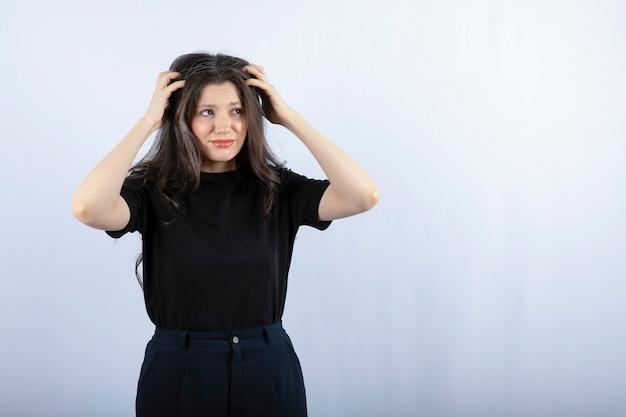 Ragazza castana che tiene i suoi capelli sulla parete bianca.