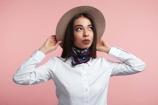 갈색 머리 소녀 그녀의 모자를 들고 핑크 스튜디오 벽 너머로 멀리보고