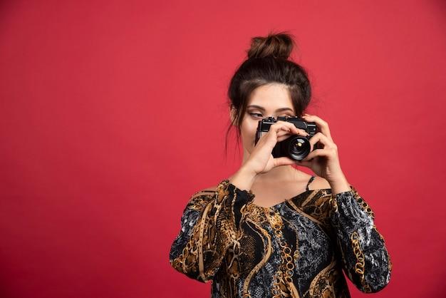 Ragazza bruna in possesso di una fotocamera reflex digitale professionale e facendo servizio fotografico.