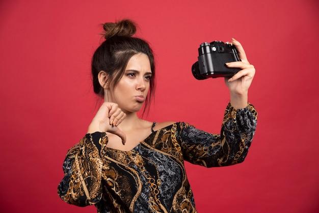 Ragazza bruna in possesso di una fotocamera reflex digitale professionale e prende i suoi selfie delusi.