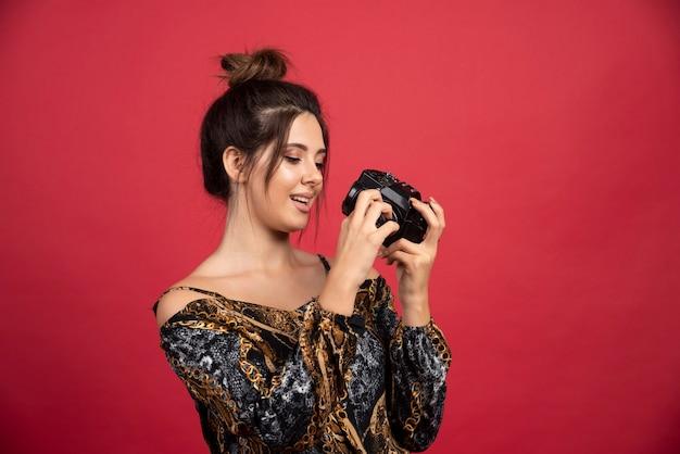 Ragazza bruna in possesso di una fotocamera reflex digitale professionale e di pensare.