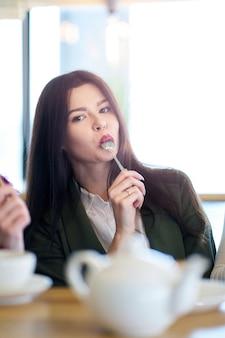 カフェで食事を楽しんで口にスプーンを保持しているブルネットの少女