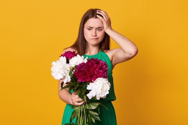Brunette girl holds big bouquet of burgundy peonies in hand, thoughtful woman with flowers keeps hand on head, poses on yellow. copy space for promotion