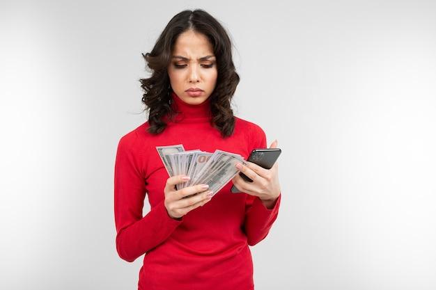 Брюнетка держит в руках свои заработанные деньги на белом фоне с копией пространства.