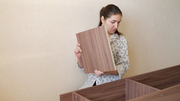 Brunette girl in home clothes sits on kitchen floor and tries to assemble prefabricated wooden cupboard parts
