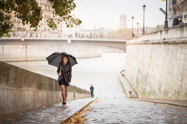 Брюнетка в черной куртке гуляет по набережной реки