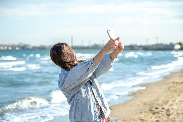 Брюнетка в джинсовой куртке делает фото на селфи-камеру телефона на фоне моря. концепция путешествий и новых впечатлений.
