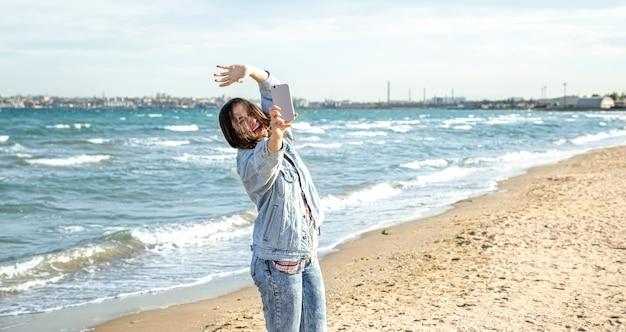 Брюнетка в джинсовой куртке делает фото на камеру телефона селфи на фоне морской стены. концепция путешествий и новых впечатлений.