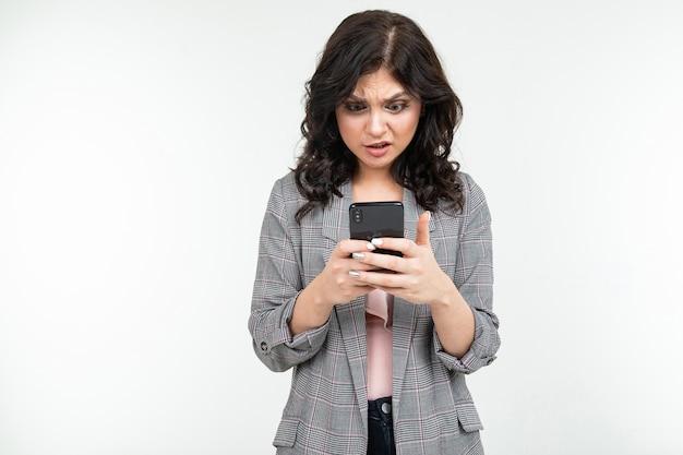 彼の手に電話を持つ灰色のジャケットのブルネットの少女は、孤立した白い背景で通信します。