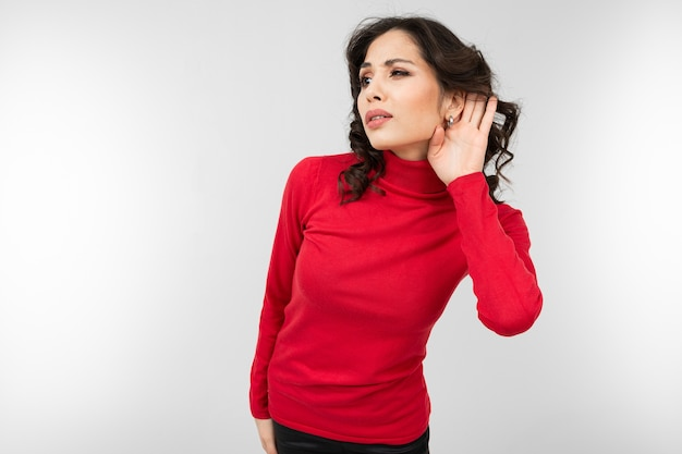 赤いセーターを着たブルネットの少女は、白いスタジオの背景で注意深く聞いている間、耳で手を握ります。