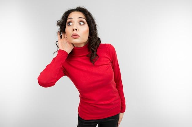 赤いセーターを着たブルネットの少女は、白いスタジオの背景で会話を聞きます。