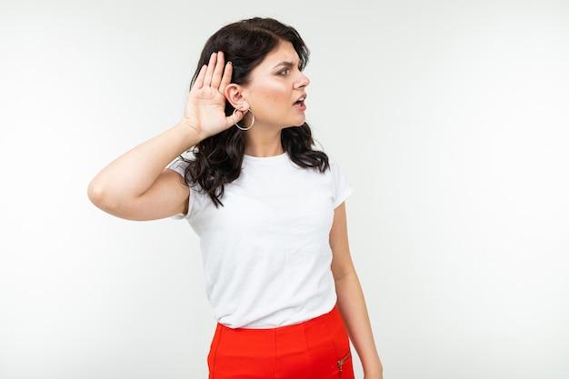 白いtシャツを着たブルネットの少女は、白の耳で彼女の手を握っている間騒音に耳を傾けます