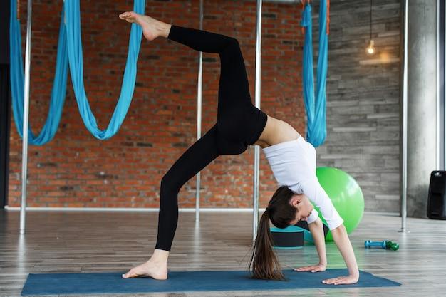 검은 색과 흰색 스포츠 옷을 입고 갈색 머리 소녀는 체육관에서 요가와 스트레칭