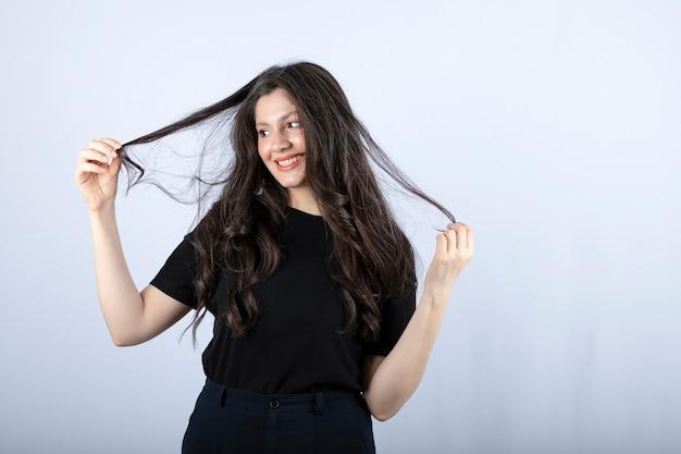 머리를 가지고 노는 검은 상단에 갈색 머리 소녀.