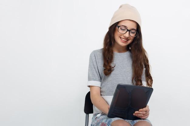 Брюнетка в очках, одетая повседневно, сидит на стуле в студии, держа в руках планшет с сенсорным экраном