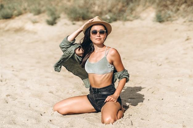 岩とビーチでリラックス帽子のブルネットの女の子