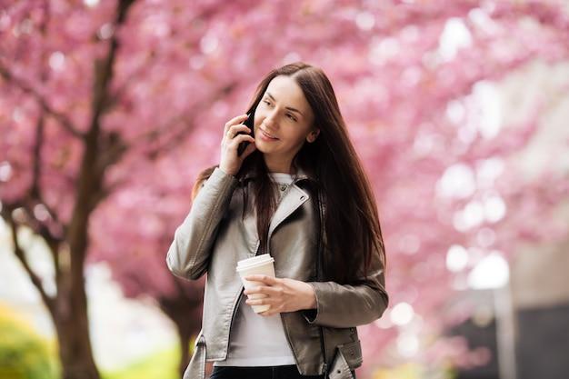 Брюнетка девушка в пиджаке и джинсах весной на открытом воздухе в городе цветущие сакуры деревья позирует
