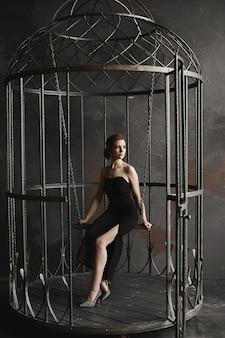 Брюнетка в длинном черном платье и ярких серебряных туфлях сидит на качелях внутри гигантской птичьей клетки
