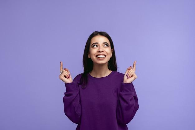 보라색 스웨터 가리키는 보라색 벽 너머로 올려 갈색 머리 소녀