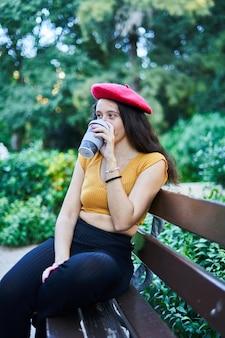 커피를 마시는 공원 벤치에 앉아 빨간 베레모에 갈색 머리 소녀