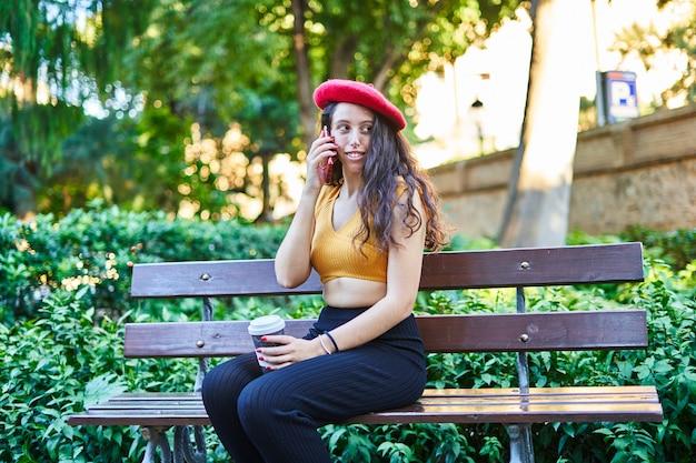 전화 통화 하는 공원 벤치에 앉아 빨간 베레모에 갈색 머리 소녀