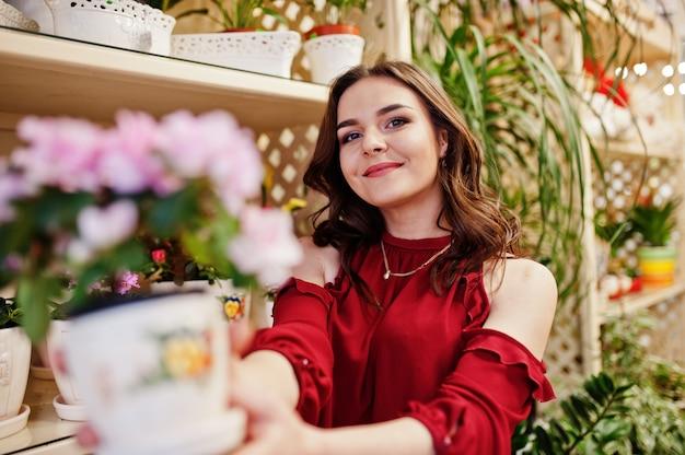 赤のブルネットの少女は、花屋で花を購入します。