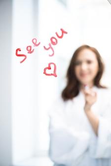Брюнетка в белом халате стоит перед зеркалом с сообщением до встречи и маленьким сердечком, нарисованным помадой