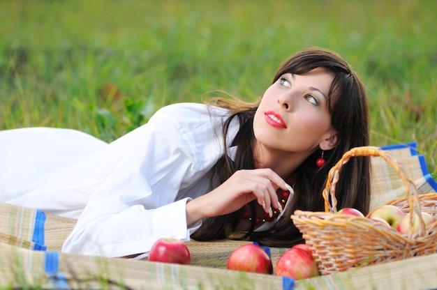 白いシャツを着たブルネットの少女は、リンゴと籐のバスケットの近くのピクニックマットの上に横たわっています。