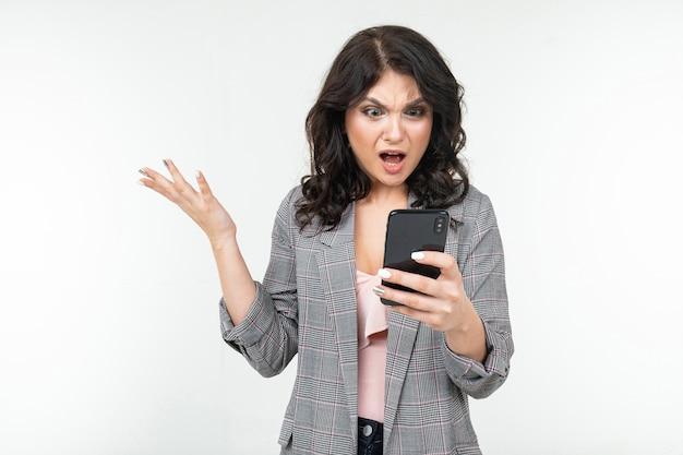 ブルネットの少女は、白いスタジオの背景に電話からの情報を憤慨して研究します。