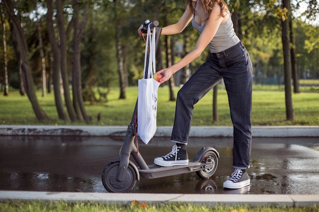 A brunette girl is standing next to electric scooter in the park and takes an apple from a bag