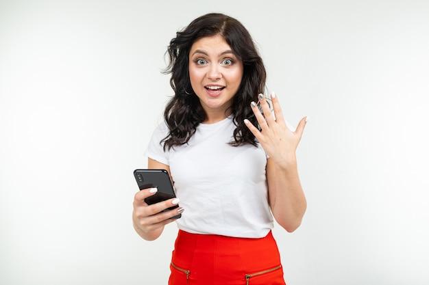 ブルネットの少女は白い分離背景に彼女の手で携帯電話を保持しているインターネットをサーフィンします。