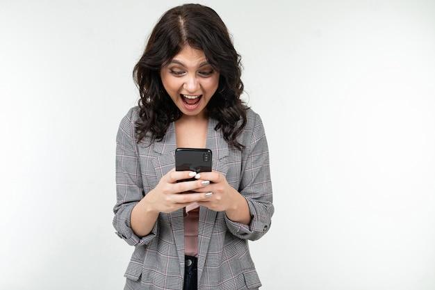 ブルネットの少女は、白い孤立した背景に彼女の手で携帯電話を保持してインターネットをサーフィンしています。