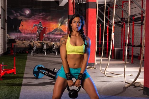 Brunette girl kettlebell swing weightlifting