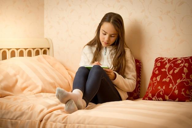 Девушка брюнетка, лежа на кровати со своим личным дневником