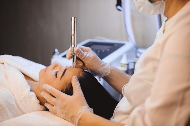 Девушка-брюнетка, лежа на диване во время спа-процедуры для кожи лица