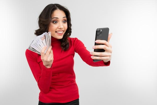 Девушка-брюнетка делает селфи с деньгами в руках с копией пространства