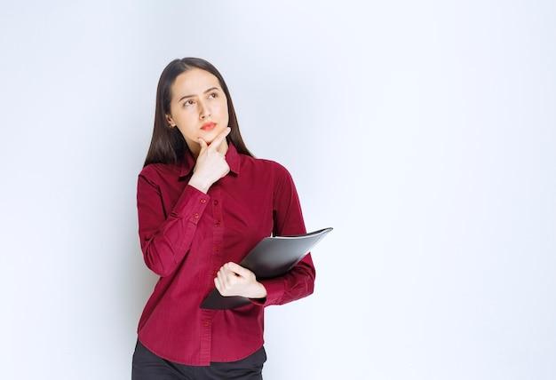 Un modello di ragazza bruna in piedi e in posa con una cartella contro il muro bianco.