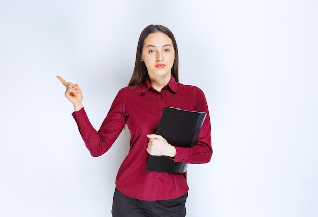 A brunette girl model standing with a folder and pointing away with an index finger.