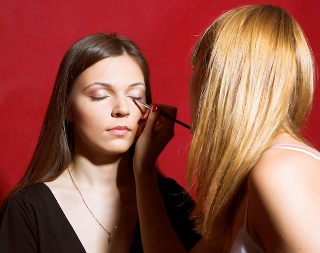 Brunette girl model, while make-up before shooting session