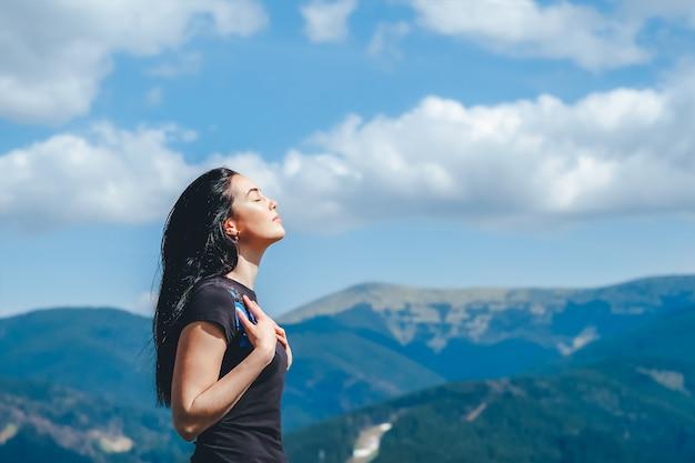 신선한 공기를 즐기는 산 위에 갈색 머리 소녀