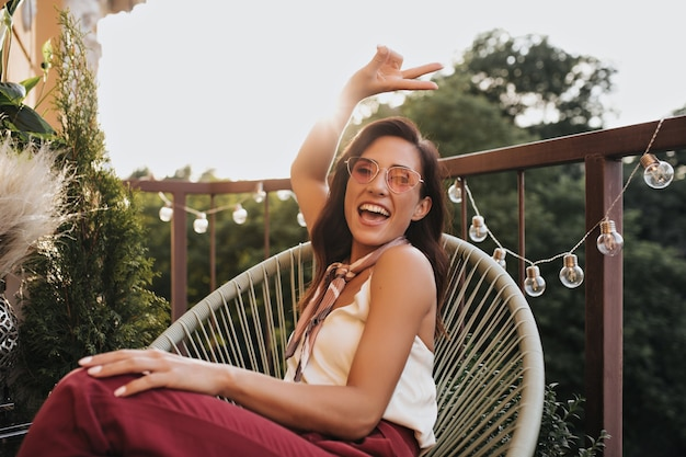 Brunette girl in pink glasses poses on balcony and shows peace sign. cheerful woman in silk scarf around her neck laughs and sits on terrace.